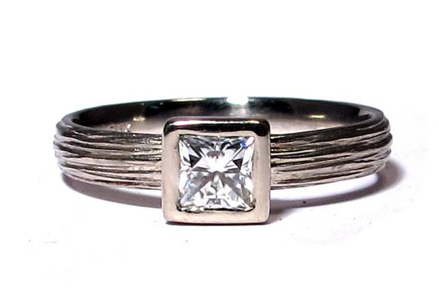 This textured Palladium band features a 4mm princess cut Moissanite, a great alternative to diamonds for cost and beauty. It comes in White Gold, Yellow Gold, Rose Gold, and Palladium. You can order a diamond if you prefer.