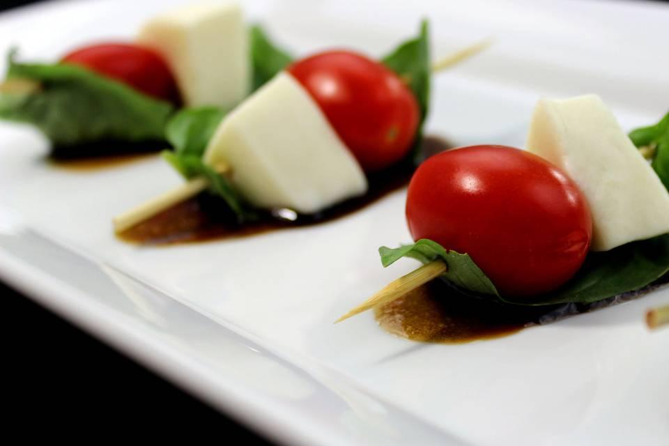 Caprese Skewers: fresh mozzarella, grape tomatoes, and basil atop a honey balsamic glaze.