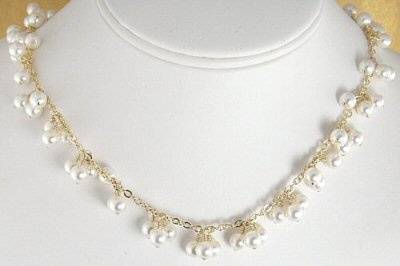 This beautiful bridal necklace is made with 6mm Swarovski pearls that have been wire wrapped onto 14-K gold filled chain. The pearls are wire wrapped onto the chain in three pearl clusters interspersed throughout. The necklace measures 17 inches and has a 14-k gold filled lobster clasp.