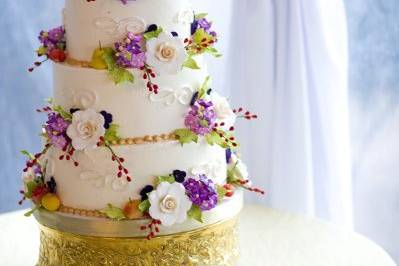 Cake is covered in sugar flowers with hand painted detail