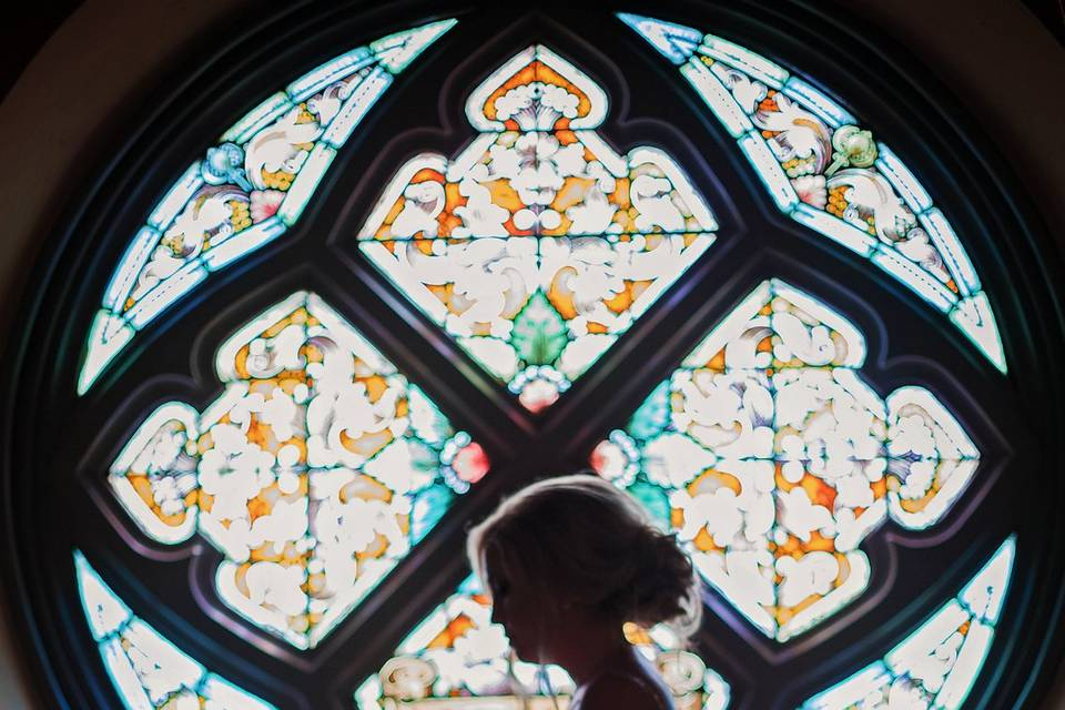 Bride beside stained glass window