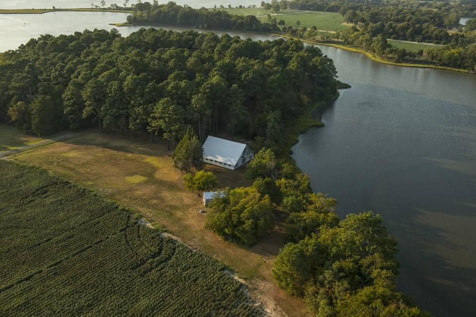 The barn nestled between evergreen trees