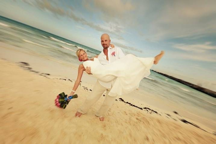 Groom carrying his bride at the beach