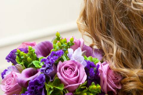 An eye catching array of purple roses and calla lilies are complimented by green hydrangea and hypericum berries.
