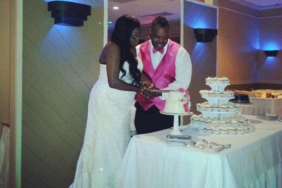 The couple cutting the cake