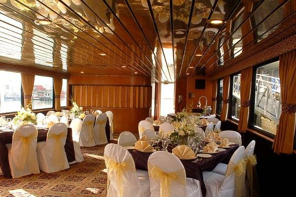 Upgraded linens, chair covers, and floral arrangements in Elite yacht main dining room.