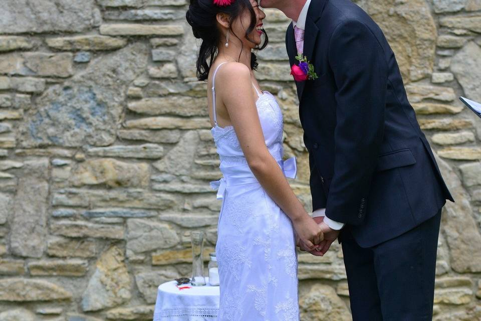 Groom kissing his bride on the forehead