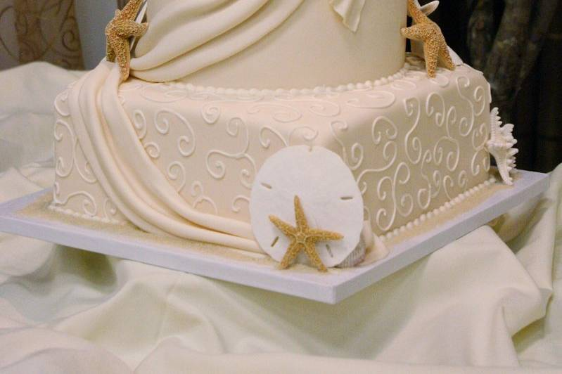 Elegant, ivory seashell wedding cake with real shells, fondant drapes, and hand-piped buttercream scrolls.