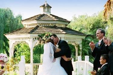 Bride and groom kissing near the gazebo at the end of the ceremony.